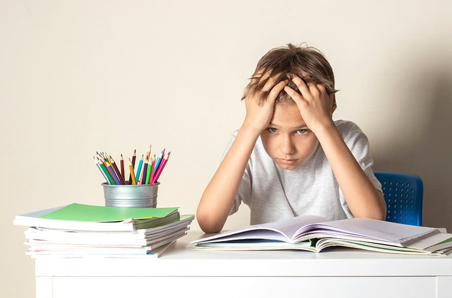 Image of a boy having trouble reading because of anxiety symptoms in children - Child Behavior Clinic